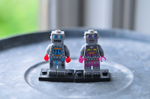 two lego robot figures with pink and blue accents