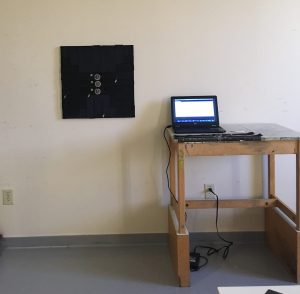 a black square mounted on an off-white wall. Next to the square sits a table that holds a laptop.
